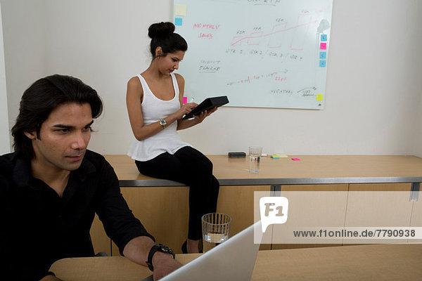 Junger Mann mit Laptop und Frau im Hintergrund