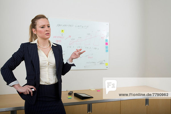 Young woman with whiteboard in background