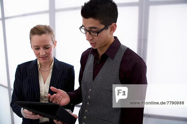 Junge Geschäftsleute mit digitalem Tablett