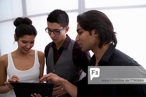 Drei junge Geschäftsleute mit digitalem Tablett