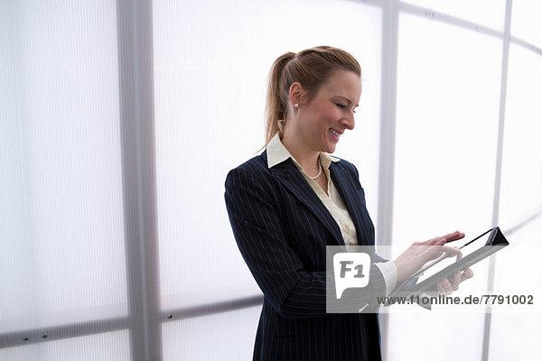 Junge Geschäftsfrau mit digitalem Tablett