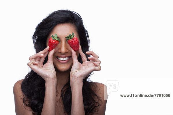 Junge Frau  die die Augen mit Erdbeeren bedeckt