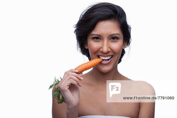 Junge Frau beißt Karotte