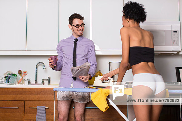 Young couple in kitchen  woman ironing in underwear