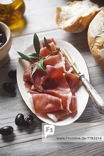 Serranoschinken mit Brot und Oliven