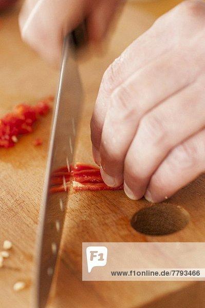 Rote Chilischote klein schneiden