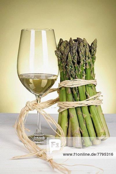 Weissweinglas und grüner Spargelbund