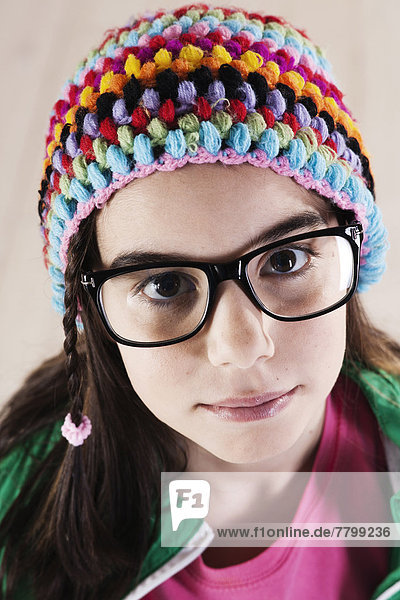 Close-up Portrait of Girl wearing Woolen Hat and Horn-rimmed Eyeglasses  Looking at Camera  Studio Shot on White Background