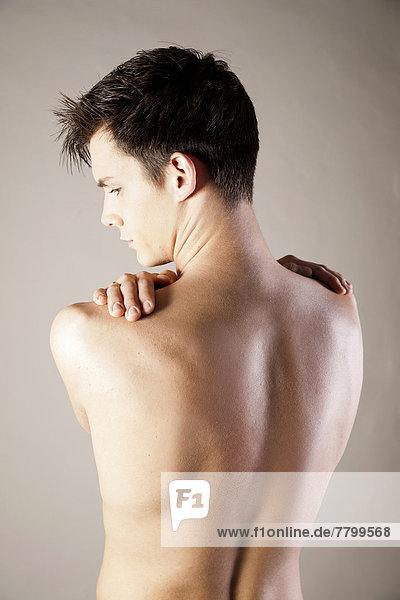 Close-up  Backview of Young Man Rubbing Shoulders with Hands  Studio Shot