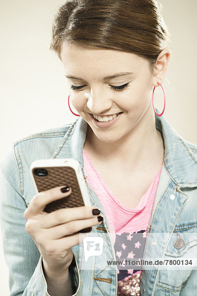 Portrait of Teenage Girl Reading Text Message on a Cell Phone in Studio