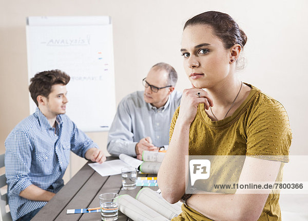 Portrait of Young Businesswoman Leaning on Hand with Colleagues Meeting in the Background