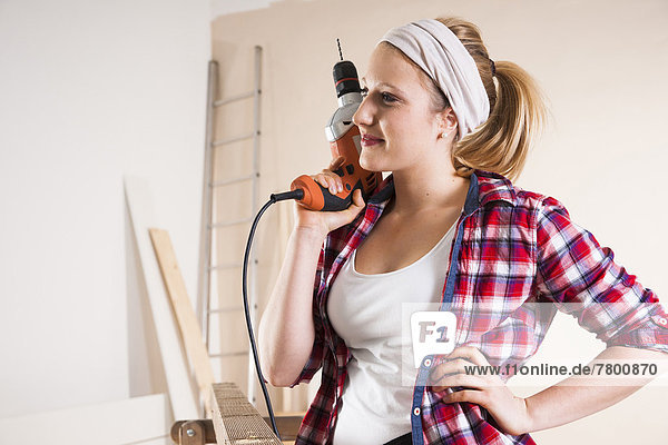 Studio Shot of Young Woman Holding Drill