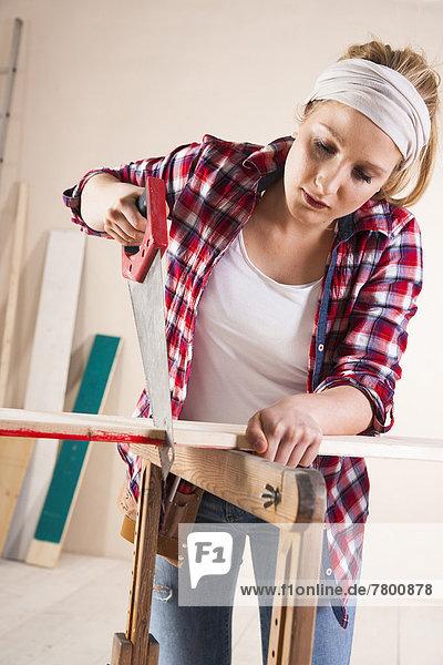 Studio Shot of Young Woman Sawing Lumber