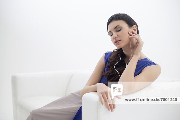 Young Woman Sitting on Sofa Listening to MP3 Player  Studio Shot on White Background