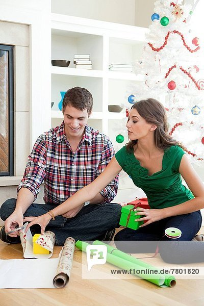Young couple sitting on floor  wrapping Christmas presents