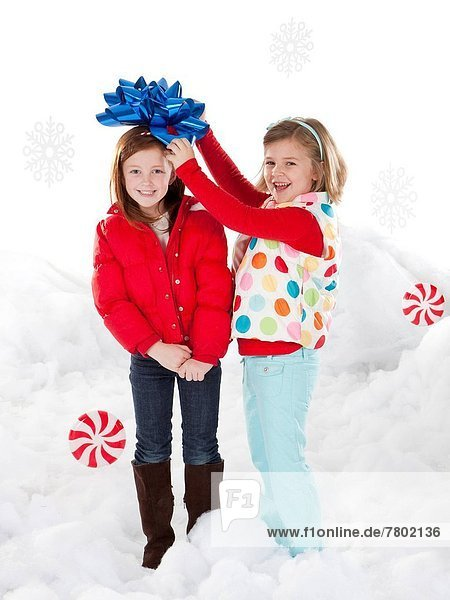 Studio portrait of girls (4-5  6-7) standing in snow