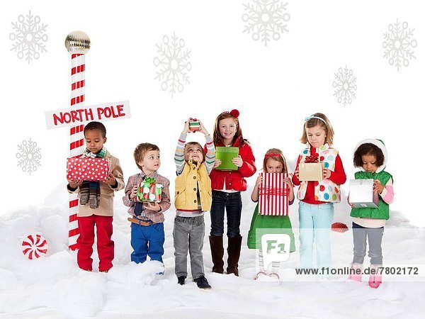 Group of kids (18-23months  2-3  4-5  6-7) standing next to North Pole sign