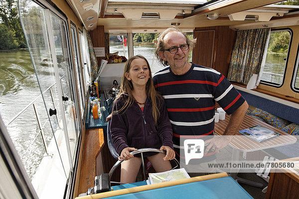 Vater und Tocher am Steuer einer Penichette  Hausboot auf der Saône