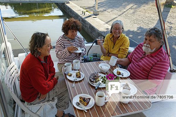 Urlauber trinken Kaffee auf der Heckterrasse einer Penichette  Hausboot auf dem Canal des Vosges  früher Canal de l?Est  im Hafen