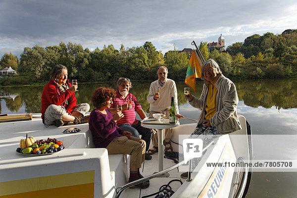 Aperitif in der Abendsonne  auf der Bugterrasse einer Penichette  Hausboot auf der Saône  ruhiger Seitenarm des Flusses  im Hafen Marina Saône-Valley