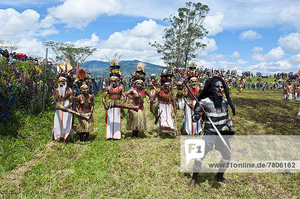 Bunt geschmückte und bemalte Mitglieder eines Volksstamms beim traditionellen Sing-sing