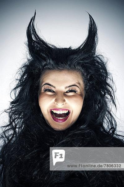 Lachende junge Frau als Teufel mit Hörnern Lachende junge Frau als Teufel mit Hörnern