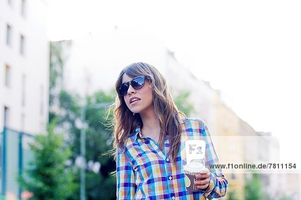 Young woman on the street with takeaway coffee cup