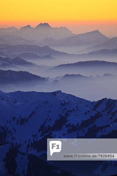 Panorama  Europa  Schneedecke  Berg  Winter  Berggipfel  Gipfel  Spitze  Spitzen  Himmel  Dunst  Schnee  Nebel  Alpen  Ansicht  Westalpen  Abenddämmerung  Bergmassiv  schweizerisch  Schweiz  Dämmerung