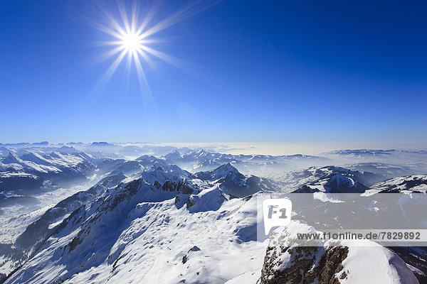 Kälte  Panorama  sternförmig  Europa  Schneedecke  Berg  Winter  Berggipfel  Gipfel  Spitze  Spitzen  Sonnenstrahl  Himmel  Dunst  Schnee  Nebel  Alpen  blau  Ansicht  Sonnenlicht  Westalpen  Bergmassiv  Sonne  schweizerisch  Schweiz
