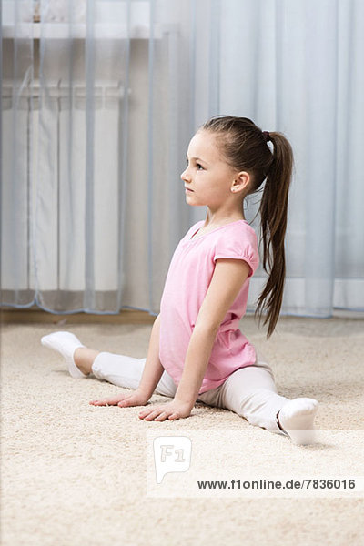 Ballerina Mädchen macht die Spagat in ihrem Schlafzimmer