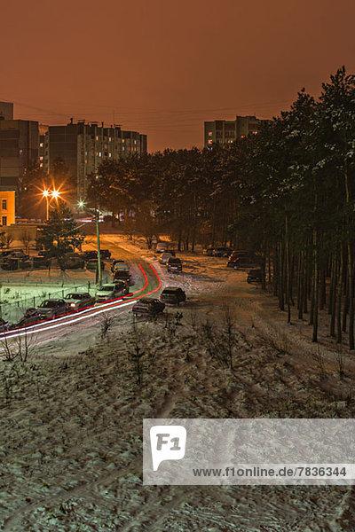 Langzeitaufnahme von Autos,  die sich nachts auf einer verschneiten Straße bewegen,  Voronezh,  Russland