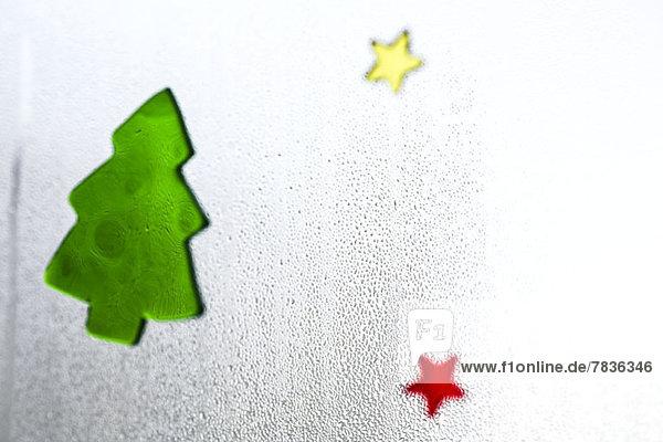 Weihnachtsaufkleber auf einem Fenster mit Kondenswasser,  Nahaufnahme