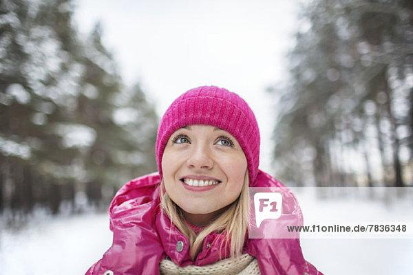 Eine schöne Frau mit Strickmütze,  die nach oben schaut,  im Winter draußen.