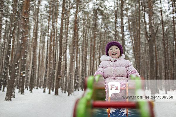 Ein junges fröhliches Mädchen auf einem Spielplatzgerät im Winter