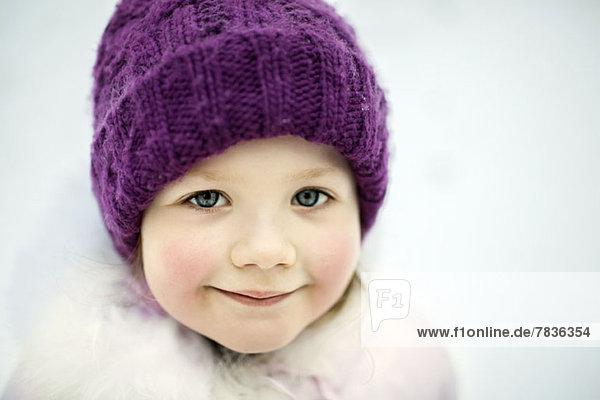 Ein junges lächelndes Mädchen mit Strickmütze,  im Winter im Freien