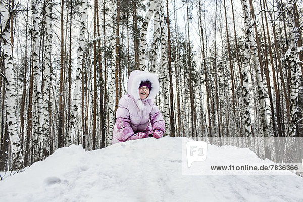 Ein junges Mädchen spielt im Schnee.