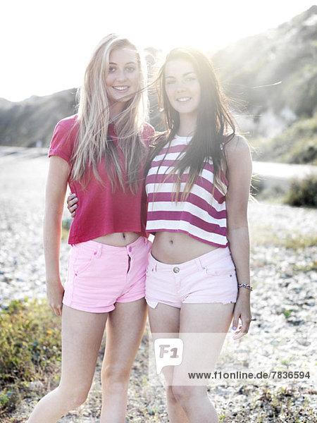 Zwei lächelnde junge Frauen  die mit den Armen umeinander am Strand stehen.