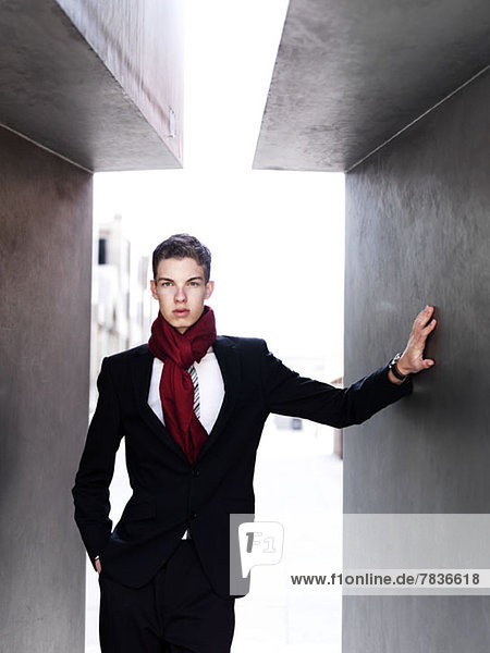 Ein modischer junger Geschäftsmann  der zwischen den Wänden posiert.
