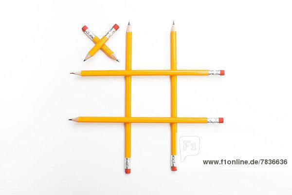 Bleistifte zu einem Tic-Tac-Toe-Spiel arrangiert mit einem einzelnen X.