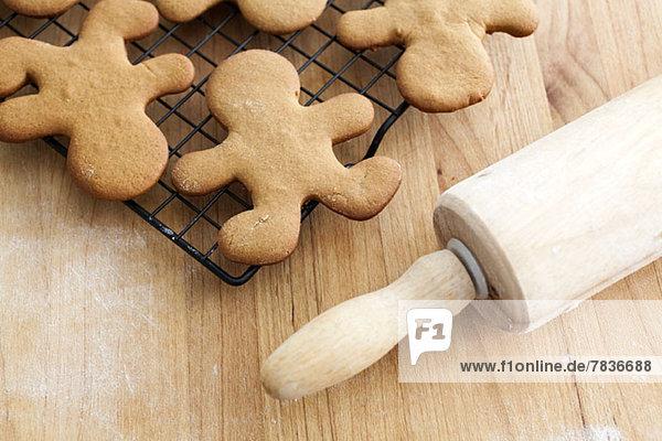 Lebkuchenmann Kekse Kühlung auf einem Gestell neben einem Nudelholz