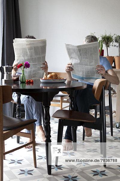 Ein gemischtes Alterspaar beim Zeitungslesen am Frühstückstisch