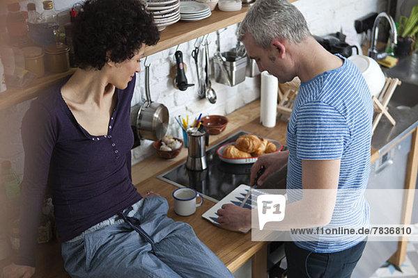 Ein lächelndes  altersgemischtes Paar  das in seiner Küche Essen zubereitet.