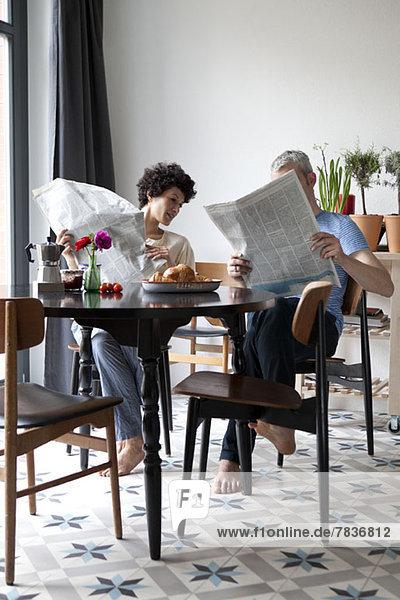 Ein angesagtes  gemischtes Ehepaar  das Zeitungen liest und frühstückt.