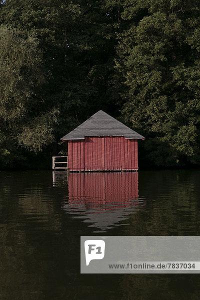 Ein rotes Bootshaus inmitten von Bäumen an einem See