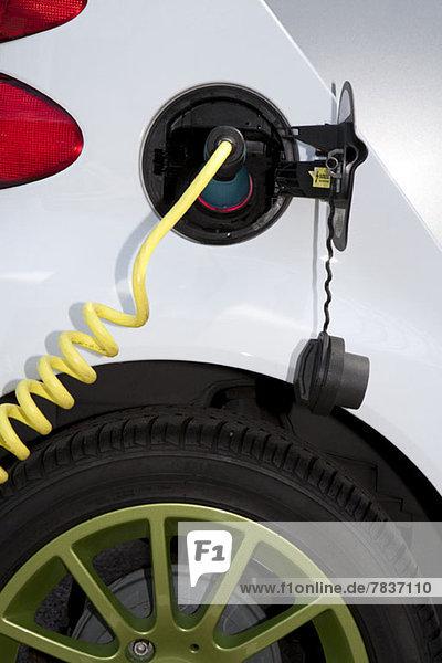 Detail eines Ladegeräts  das an das Aufladen eines Elektroautos angeschlossen ist. Detail eines Ladegeräts, das an das Aufladen eines Elektroautos angeschlossen ist.