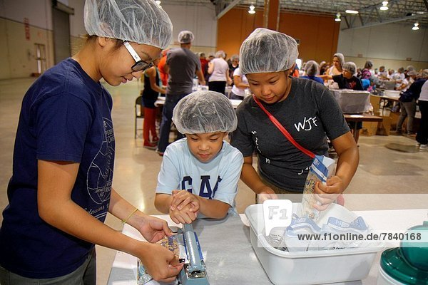 Florida  Miami  Miami-Dade County Fair And Expo  Feed My Starving Children  volunteer  community service  packing  meals  hairnet  Asian  girl  teen  boy .