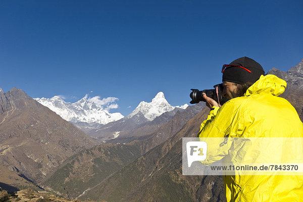 Fotograf mit gelber Jacke fotografiert Mount Everest vom Aussichtspunkt des Everest View Hotel aus