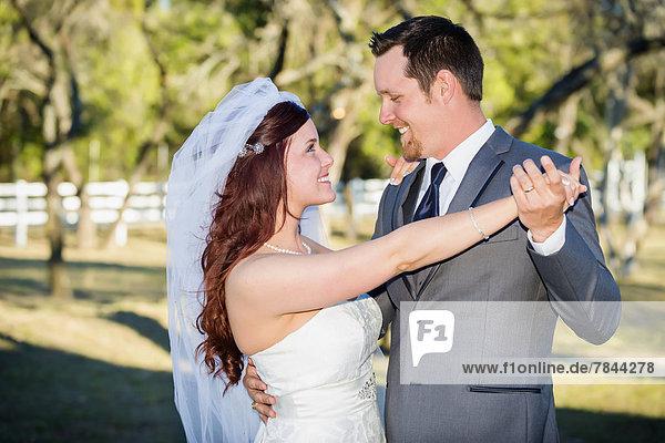 USA  Texas  Junges Hochzeitspaar schaut sich an  lächelnd