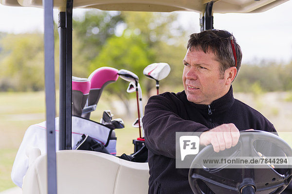 Erwachsener Mann  der auf dem Golfplatz reitet