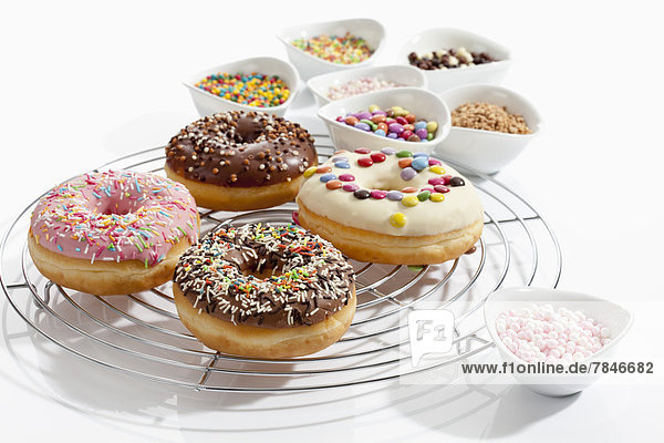 Variety of doughnuts on cooling rack besides bowl of sprinkles